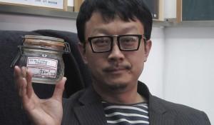 Liang Kegang con el frasco subastado.